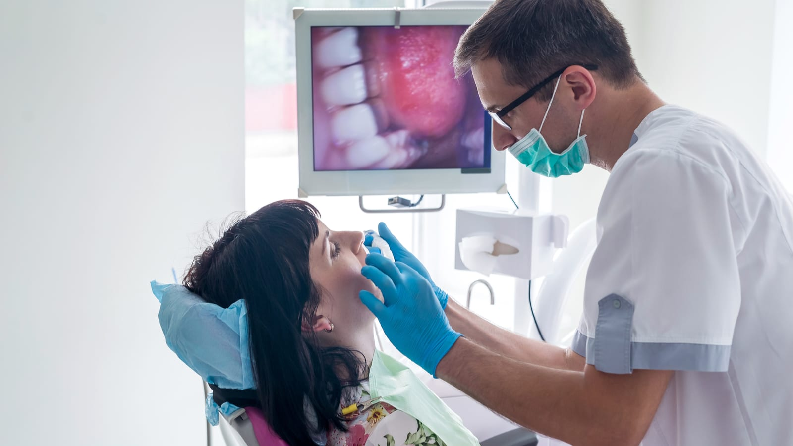 Dentist examining patient with intraoral camera
